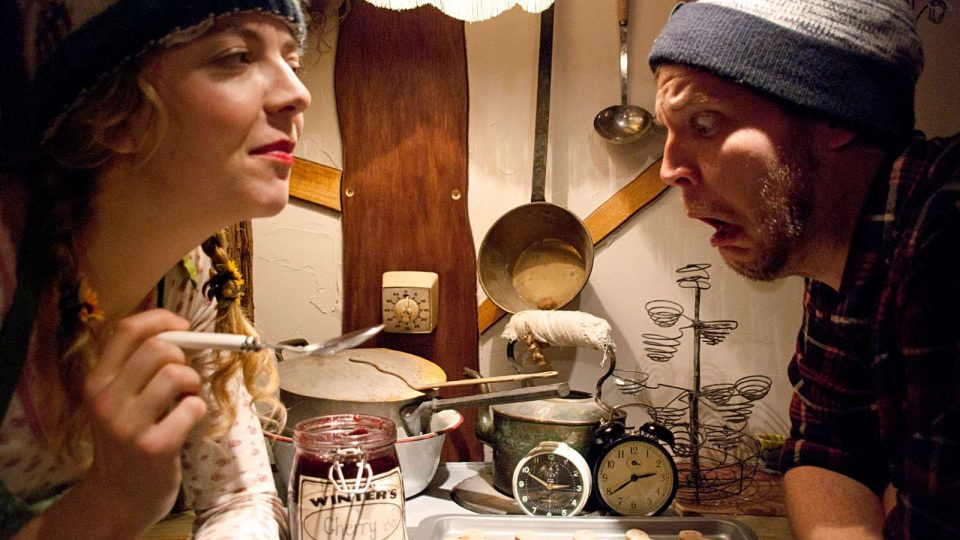 Two performers sat down in a kitchen setting. One of the left holding a spoon and the performer on the right looking shocked
