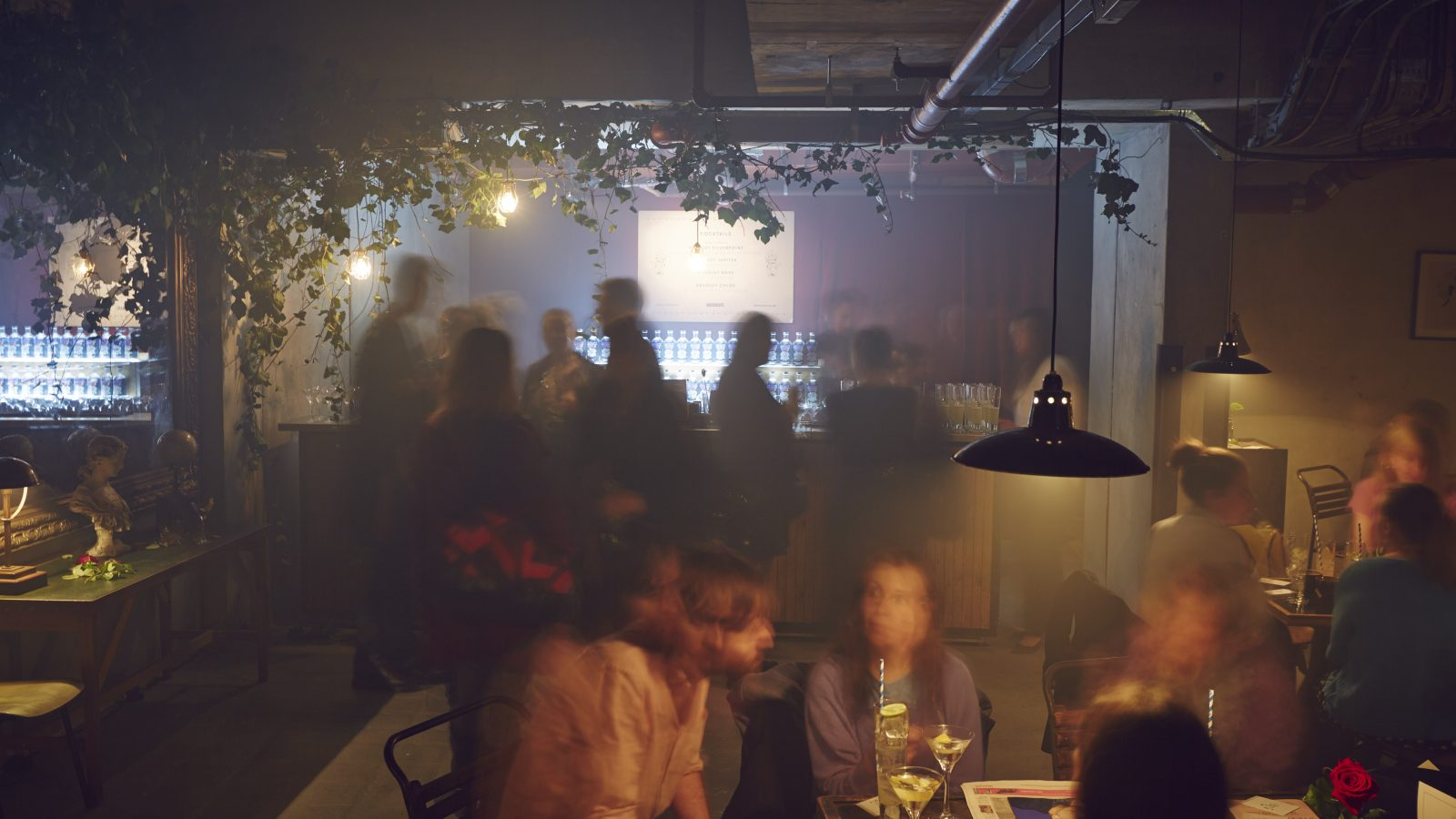 Blurred image of a bar setting with various group of people sitting at tables and standing by the bar