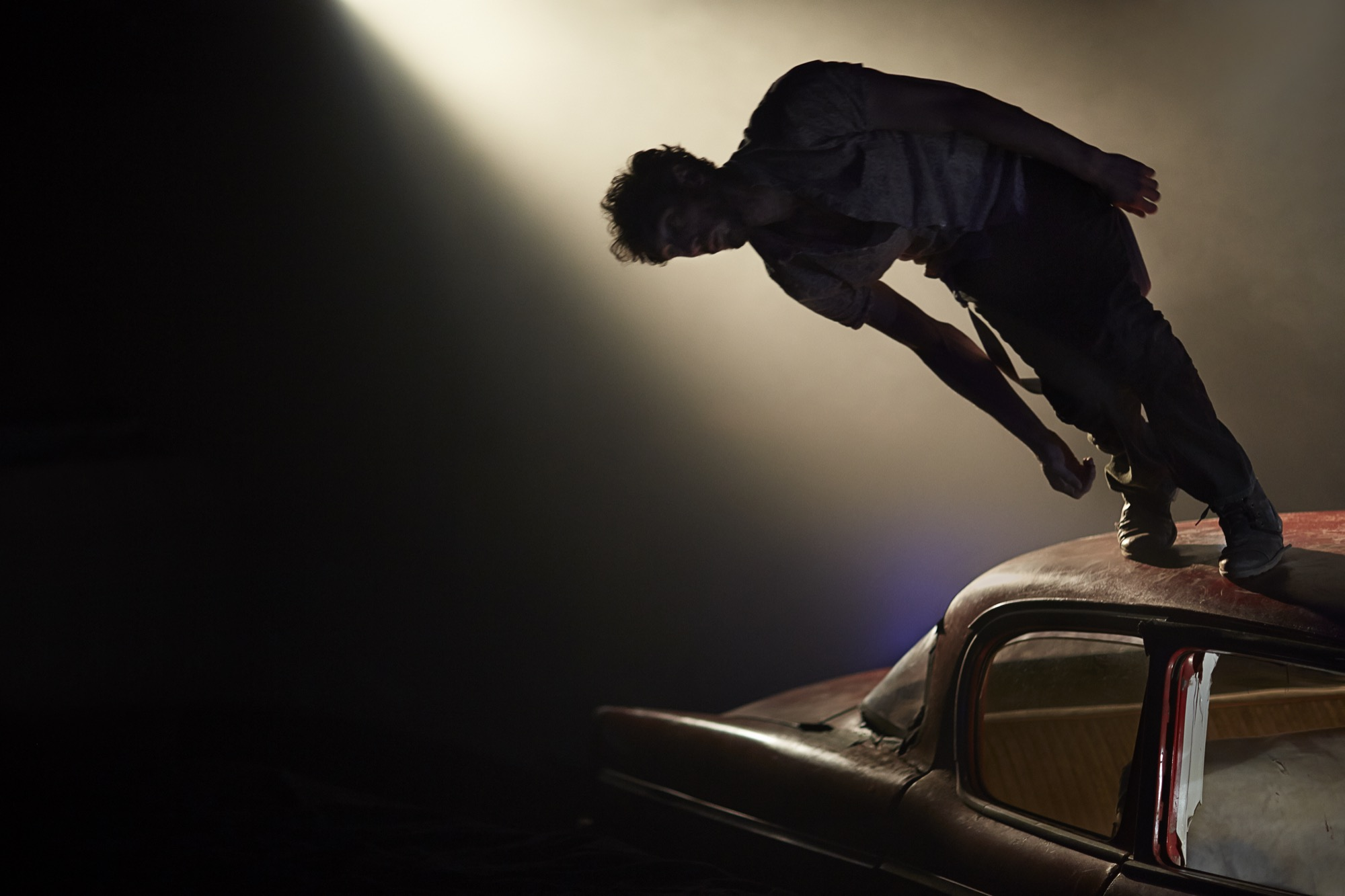 Man falling of the roof of a vintage car