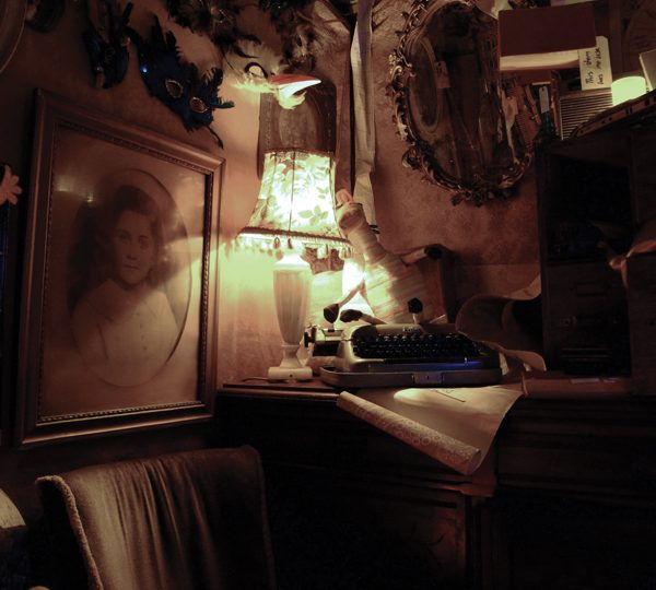 Close up of bric-a-brac (lampshades, masks on the wall, vintage photos and a typewriter on a table)