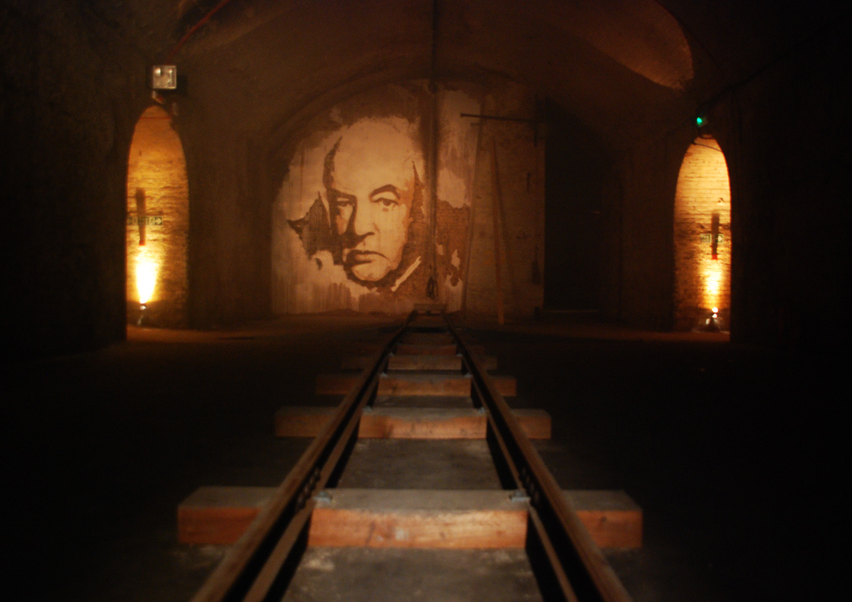 Close of train tracks with image on the wall