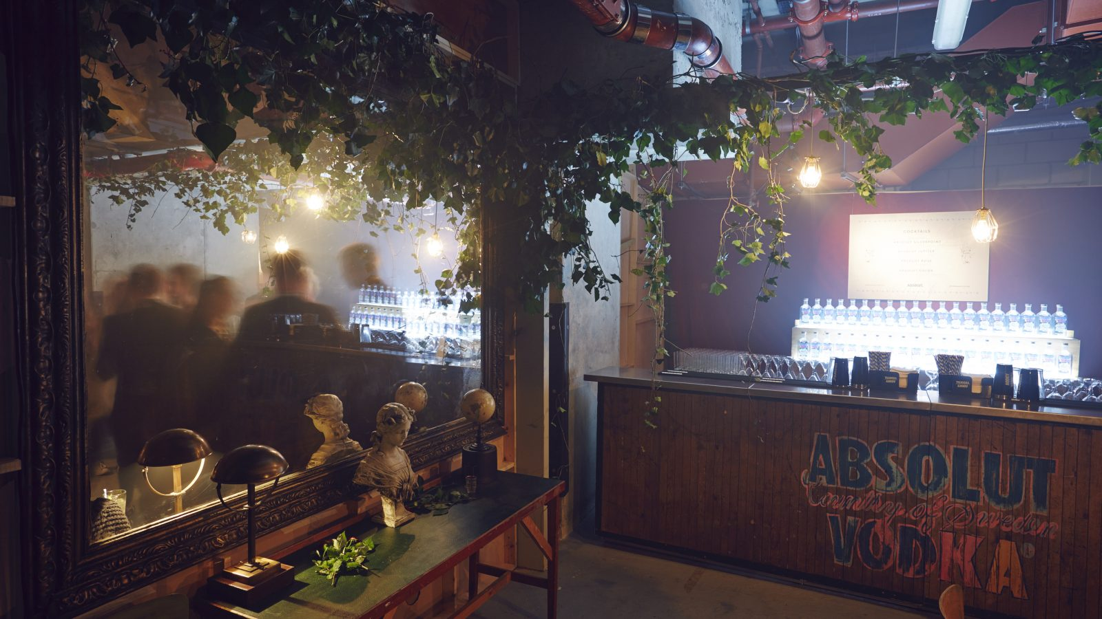 An empty bar with the 'Absolut Vodka' logo on the front of the bar; large mirror and decorative items around the bar