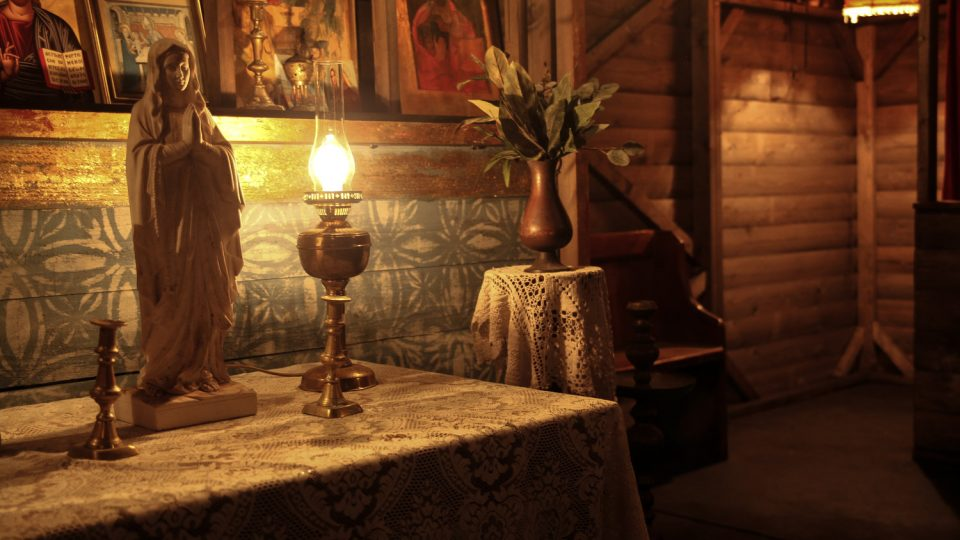 A mini statue and some lamps on top of a table with some religious pictures on the wall behind.