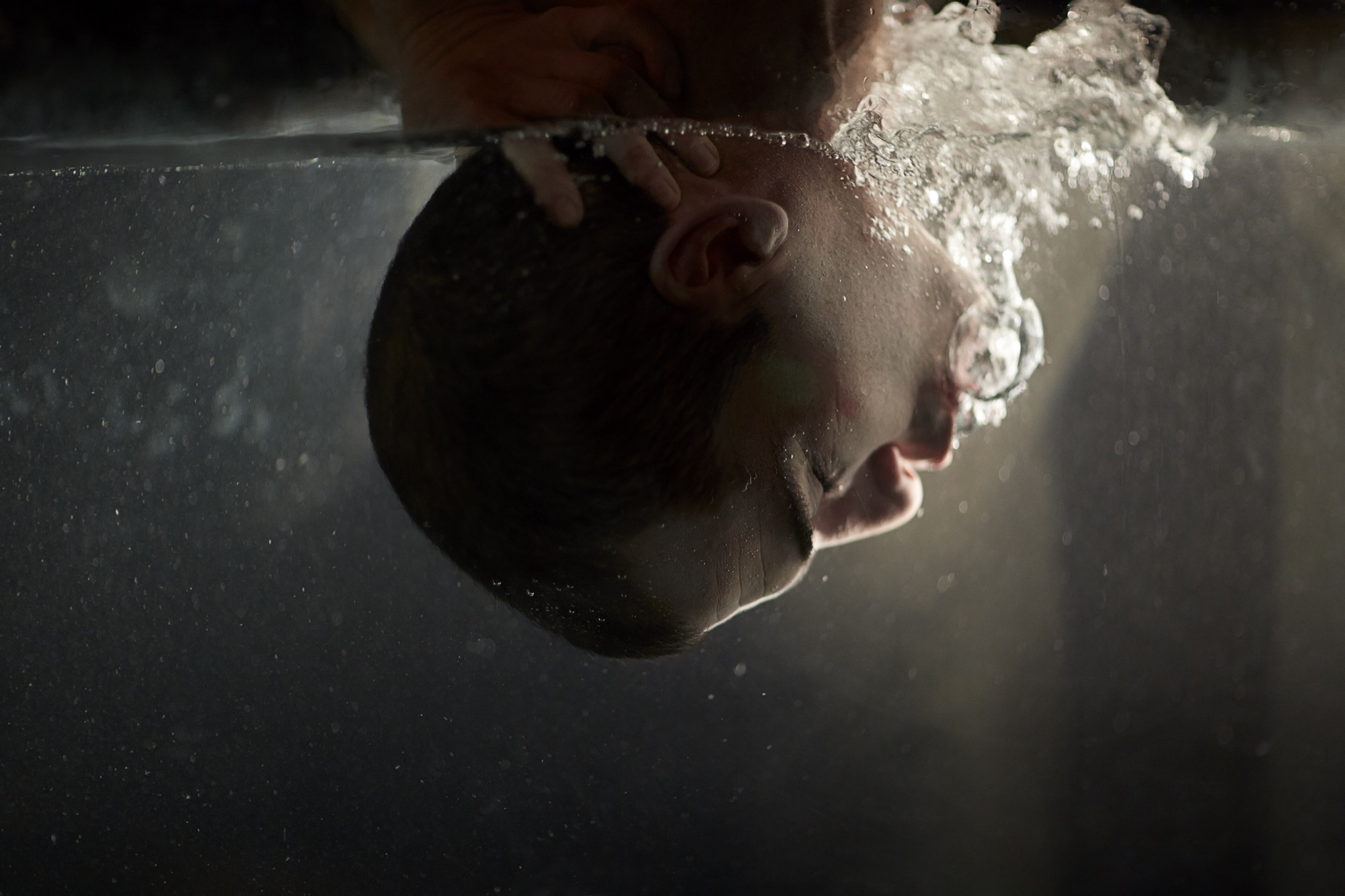 A man's head being pushed underwater.
