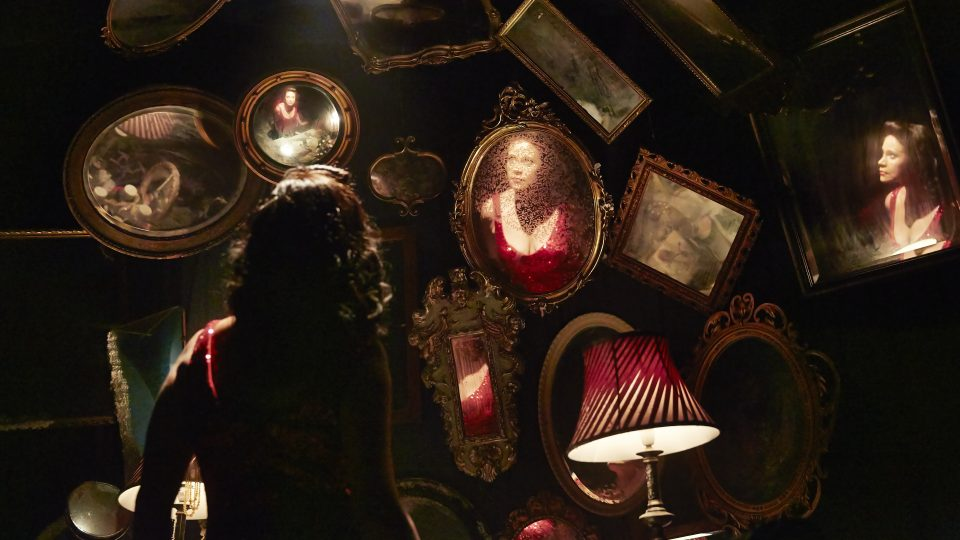 A woman stood with her back to the camera, with walls covered in mirrors.