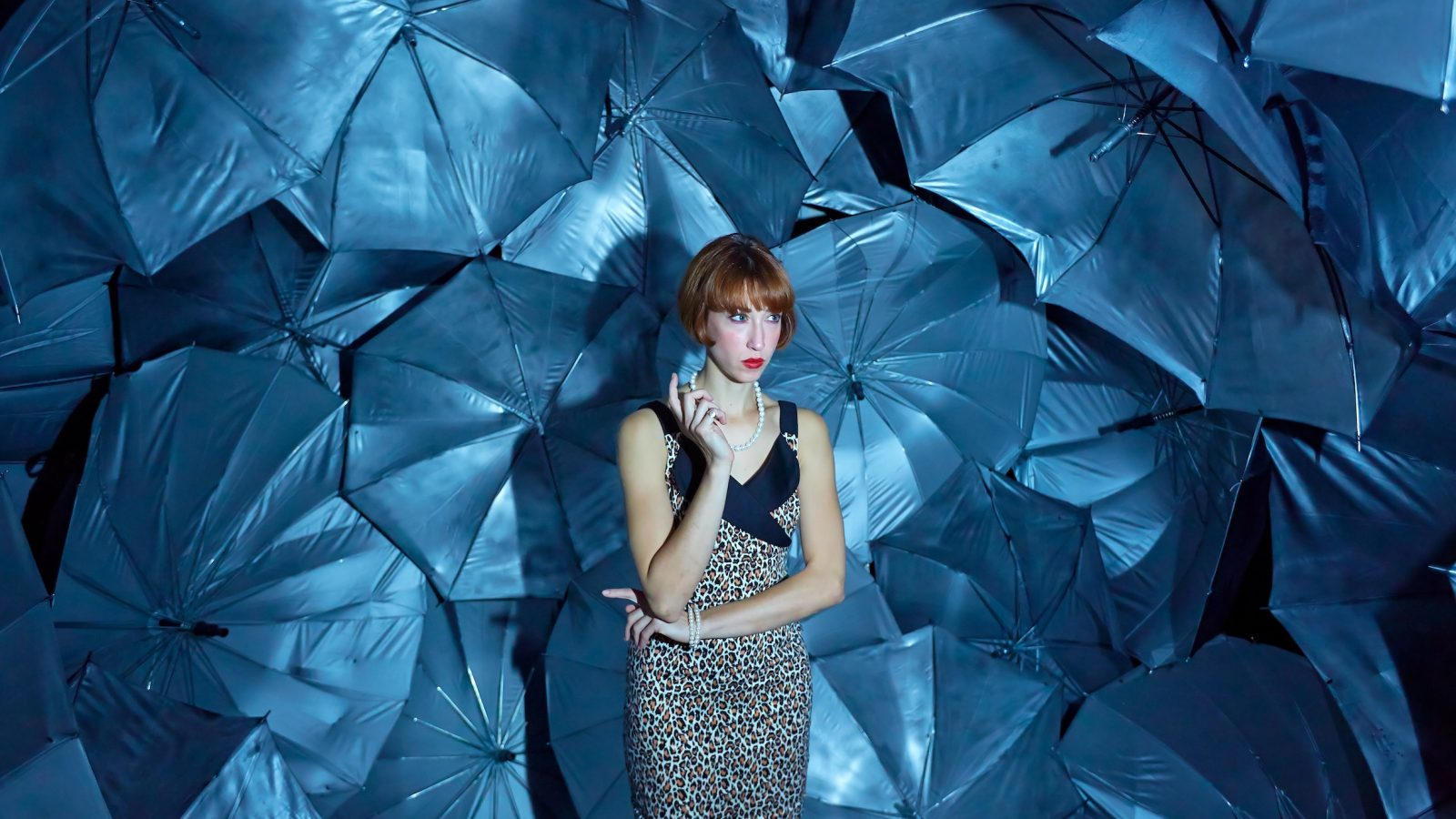 A woman stood infront of a wall made of blue umbrellas smoking.