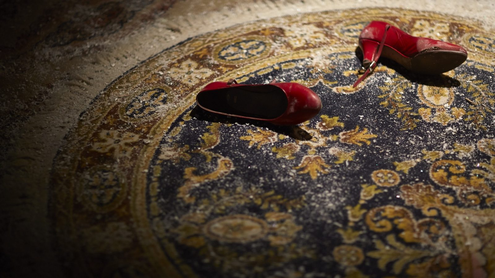 Pair of red shoes ontop of a dusky rug