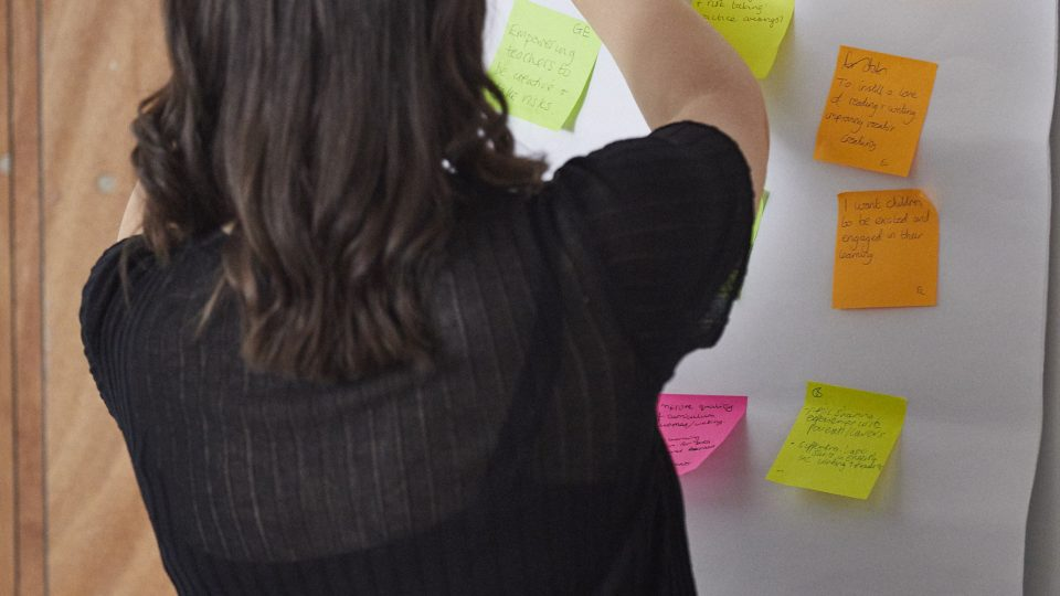 Woman adding post it notes onto a board