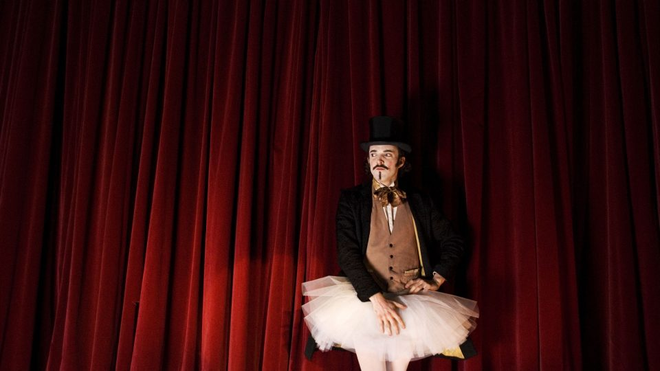 Man wearing top hat and tutu standing in front of stage curtains