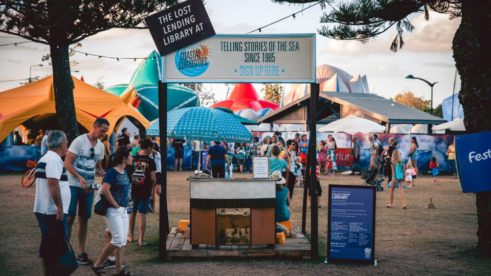 A sign with The Lost Lending Library location in the middle of an outdoor festival setting