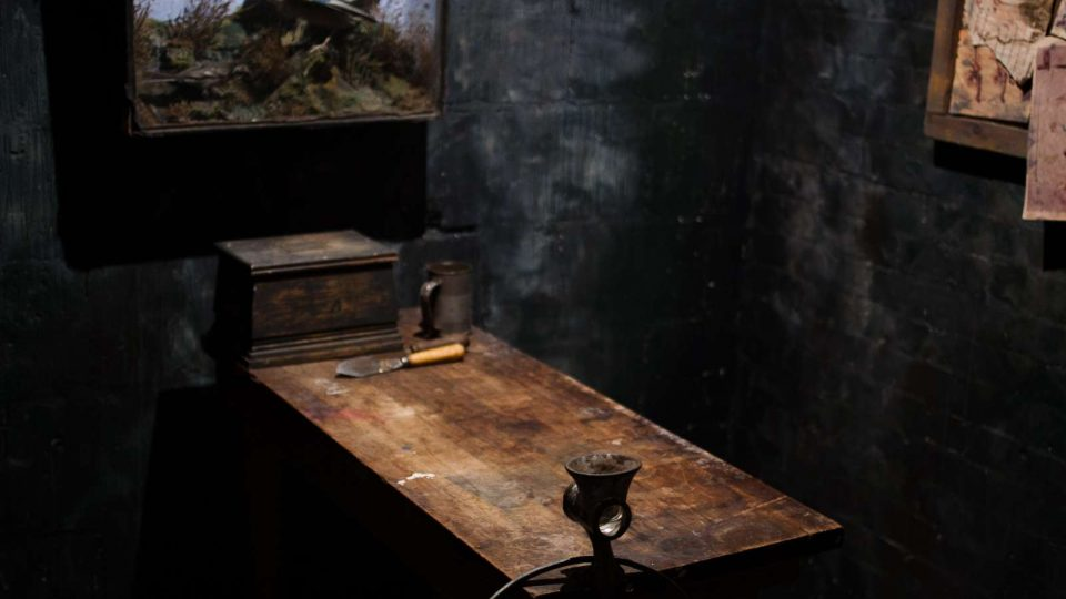 Various pots, pans and old kitchen equipment on top of an old wooden cabinet in a dark room