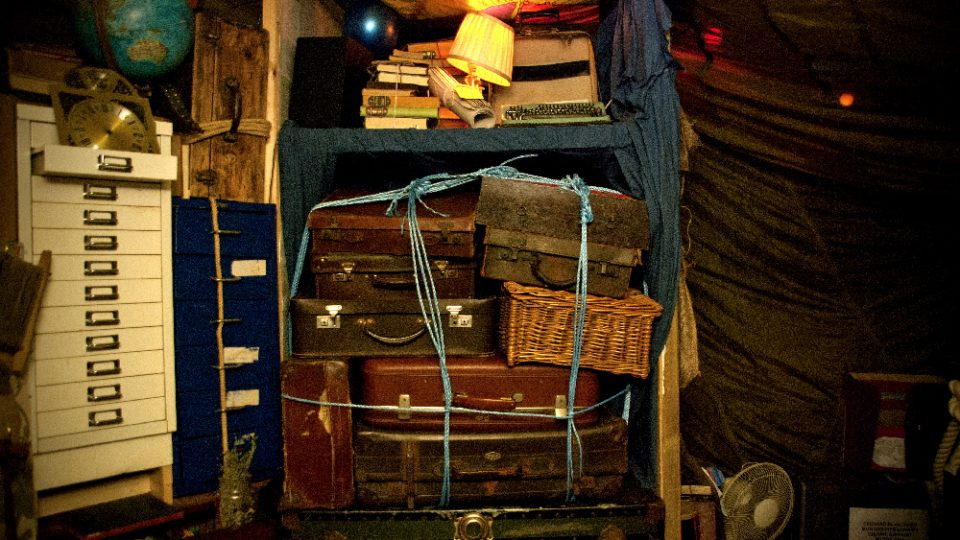 Various cases and boxes tied together underneath a table. Books, lamps, filing cabinets and other various material on and around the table