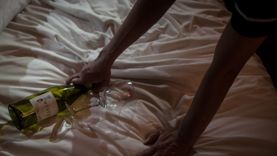A woman's hands picking up a wine glass off a hotel bed.