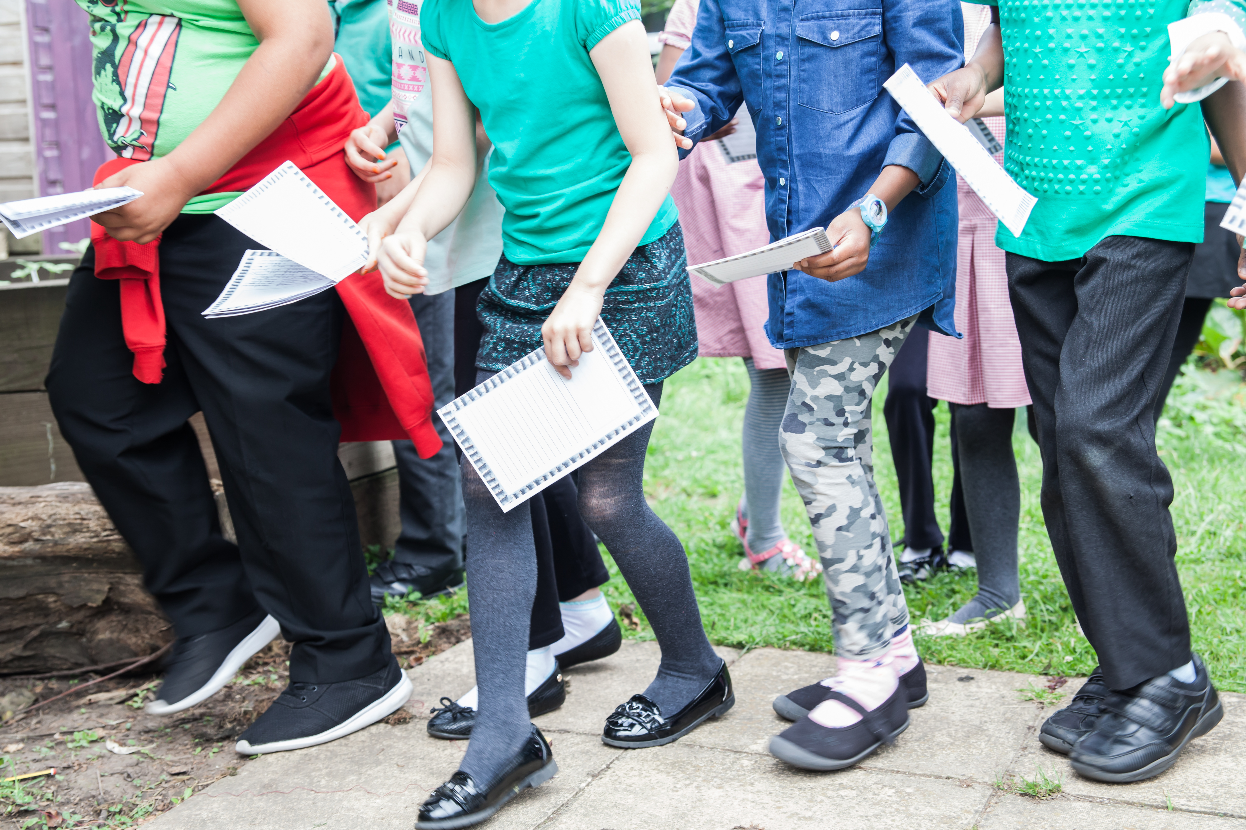 Group of children walking and holding pieces of paper