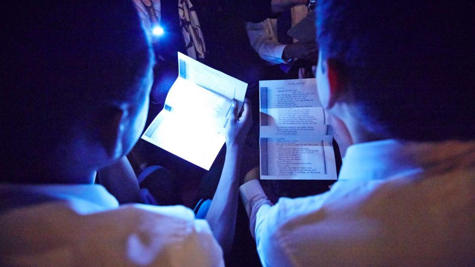 Two pupils holding pieces of paper with another shining a light on one of them