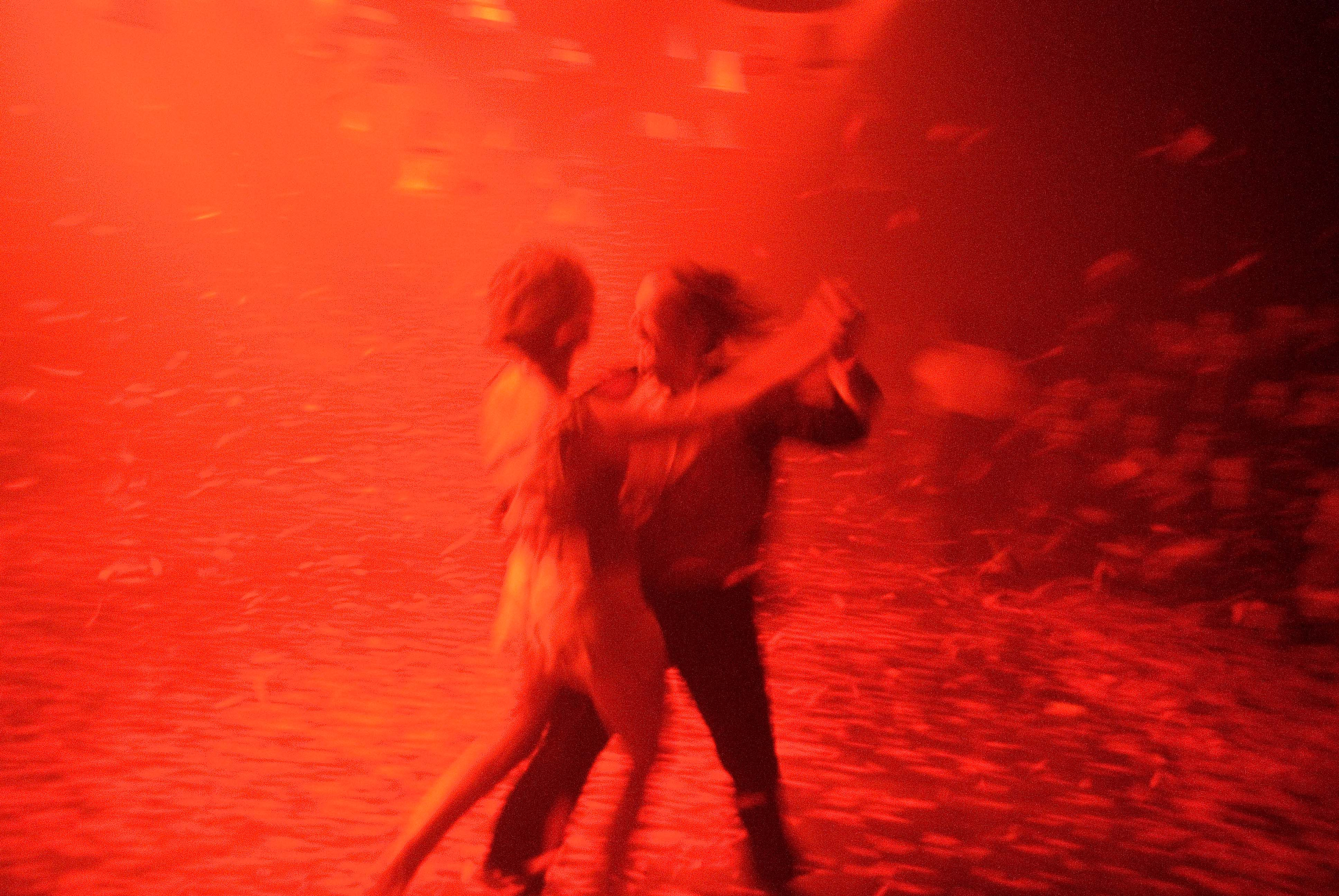 Two blurred figure dancing with each other in red lit room
