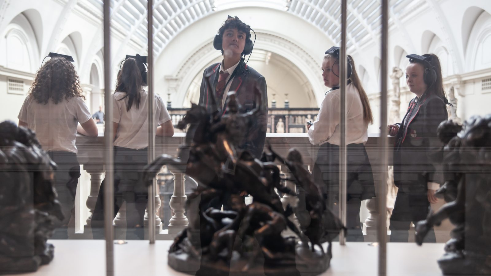 Secondary school students wearing headphones looking into a glass case.