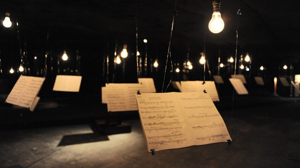 A number of hanging lights and sheet music hanging form the ceiling