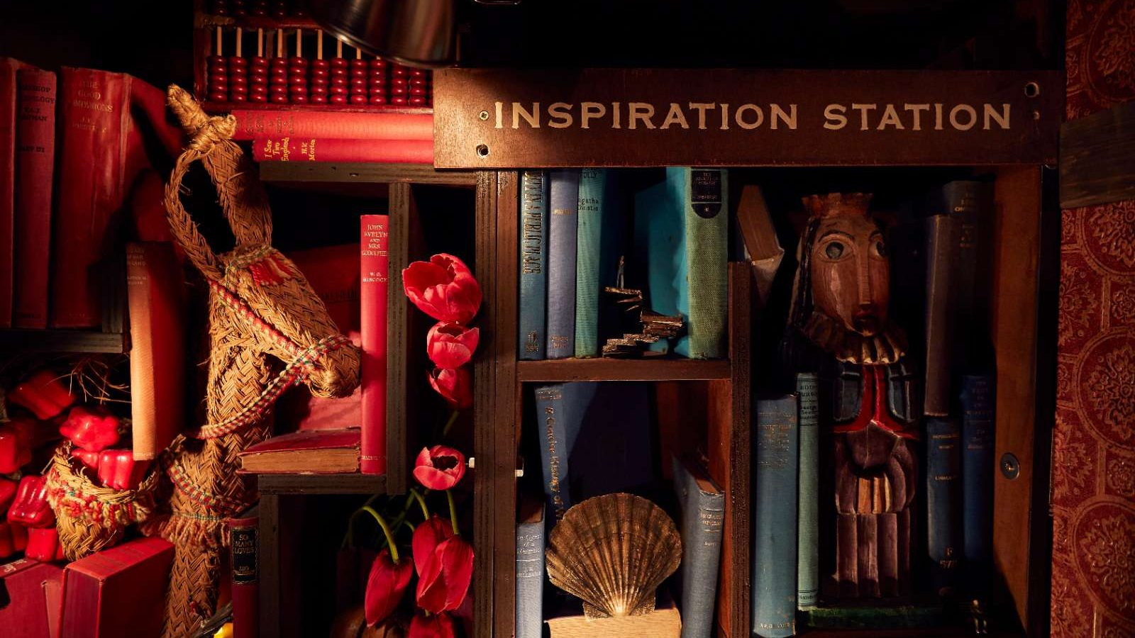 Close up of various bric-a-brac include books, flowers and ornaments on cupboard built into the wall. 'Inspiration Station' sign.