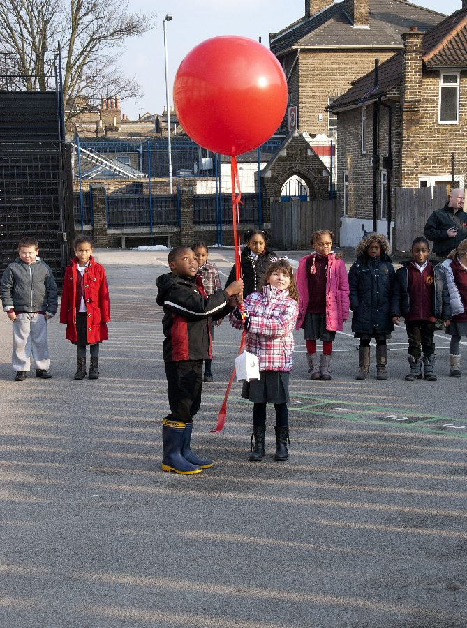 Two children holding a big red balloon in a playground with other children around them