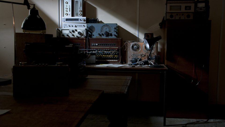 Large desk in a dark room with various sound equipment