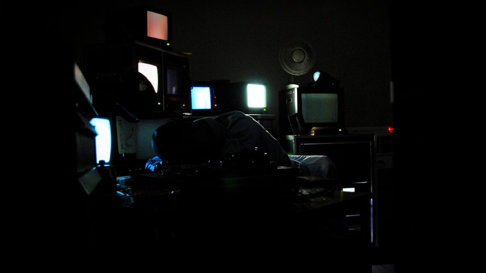Dark room filled with mini TV's and a silhouette in the centre