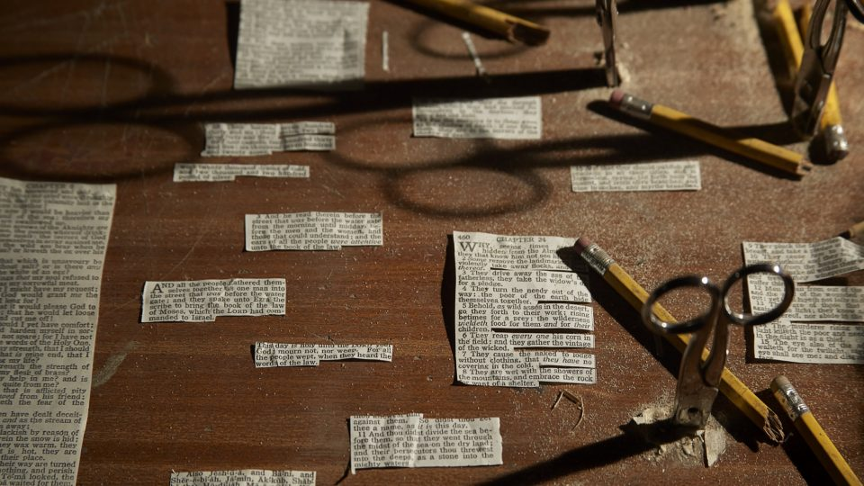 Close up of small newspaper clippings, scissors and pencils on a table