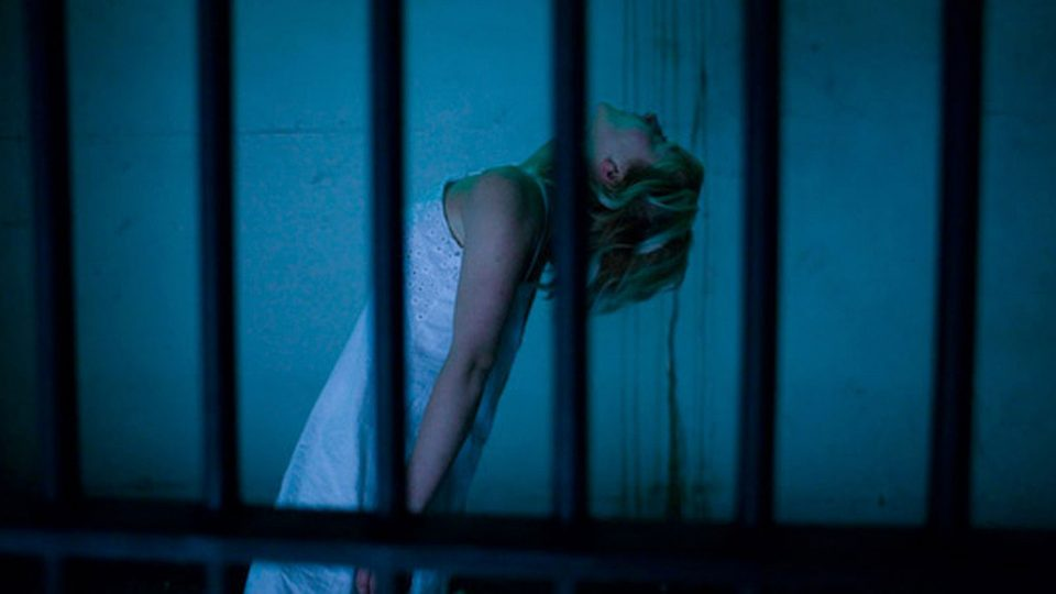 A woman behind bars is bending backwards and looking at the ceiling