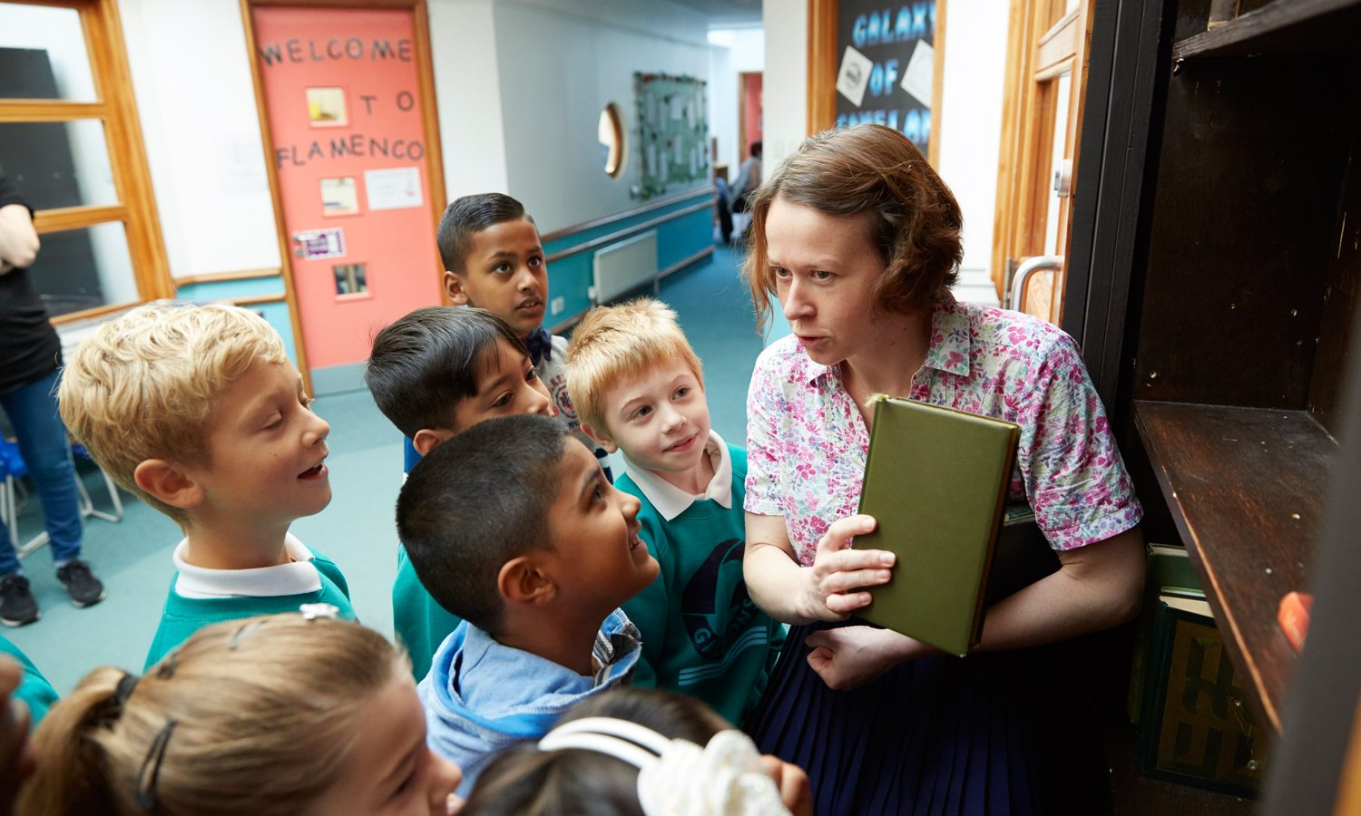 Adult performer holding a book and speaking to a group of young pupils in a school hallway