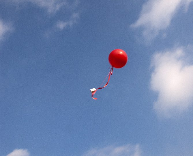 Red balloon floating away into the sky