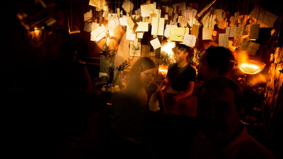 People in a dark room with letters hanging from the ceiling