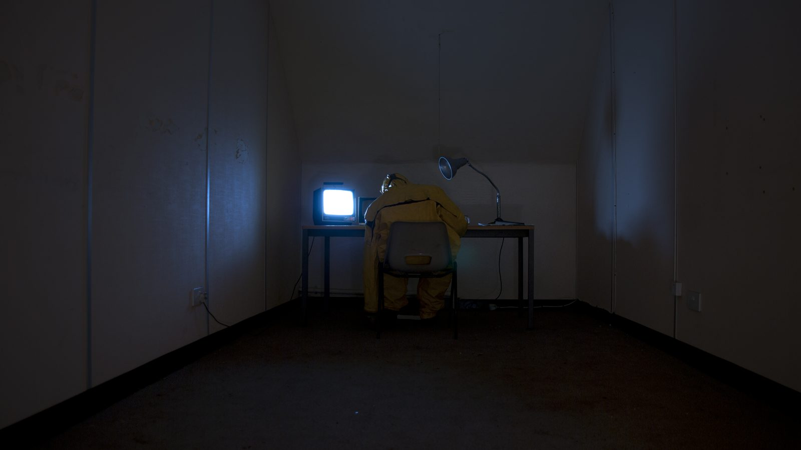 In a dark room, someone in sanitation overalls sits at a desk with a mini tv