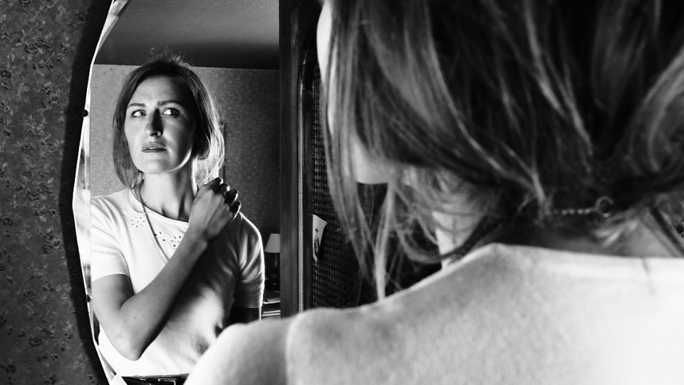 Black and white image of a woman looking at herself in a mirror