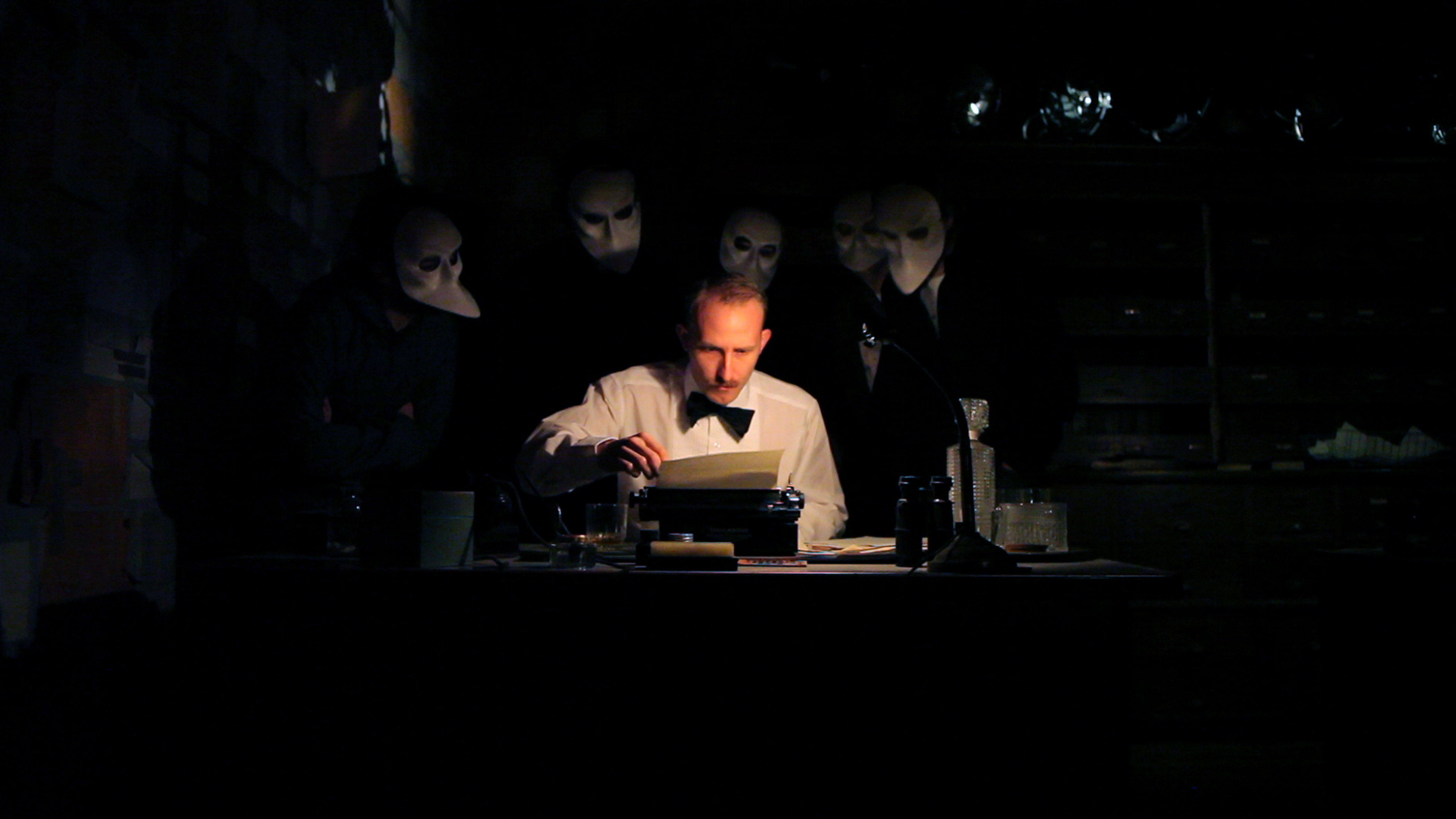 Spotlight on a man sat at desk using a typewriter surrounded by masked onlookers