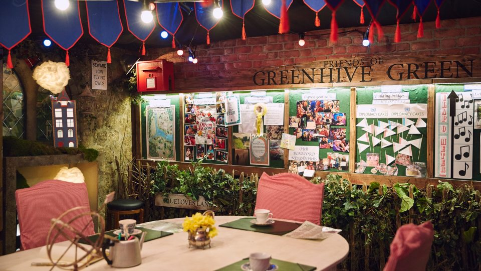 Partly shown table with teacups on it and empty chairs. A wall with 'Friends of Greenhive Green' text on it has boards covered in photos and notes.