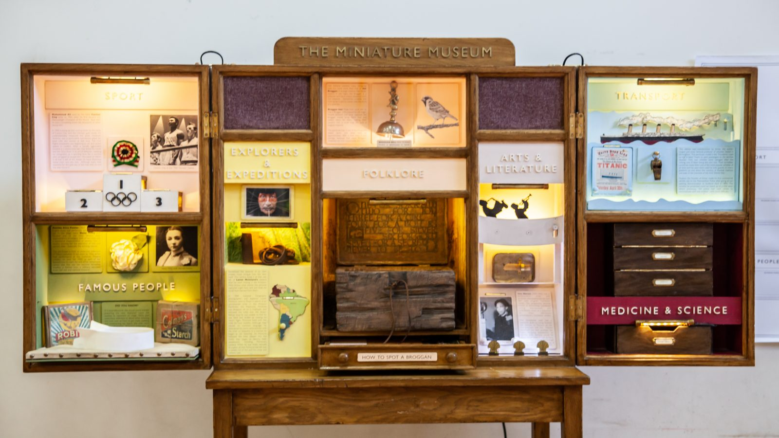 A large wooden cabinet with lots of different sections devoted to local history.