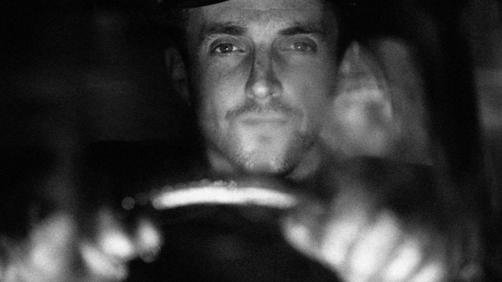 Black and white close up of a man driving