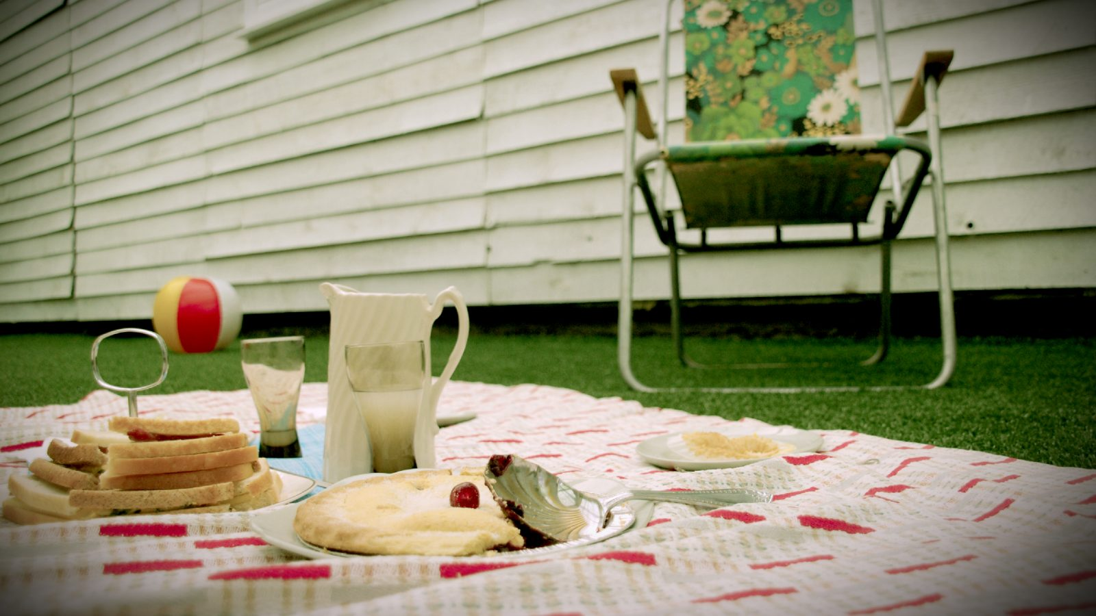 Picnic blanket, green grass and deckchair.