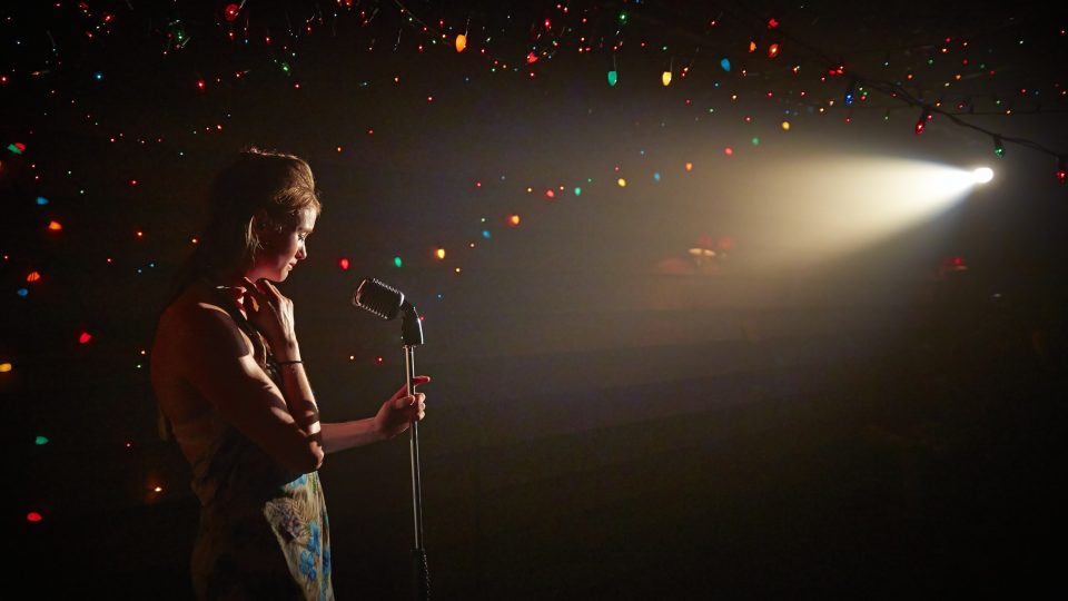 A woman holding a mic with stand. A spotlight is on her with rainbow lights surrounding