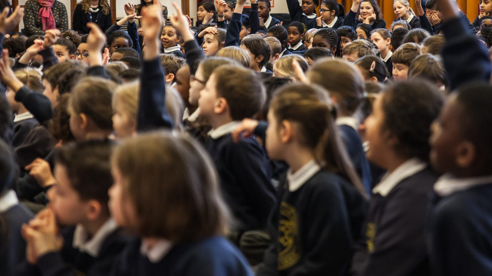 A school assembly. Lots of children with their hands up.